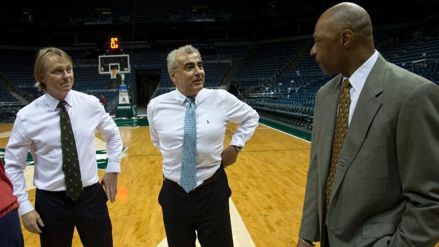 New York investment firm executives Marc Lasry , left, and Wesley Edens talks to Milwaukee Bucks assistant coach Jim Cleamons Wednesday, April 16, 2014, in Milwaukee. The Bucks announced that owner Herb Kohl has reached a deal to sell the franchise to Edens and Lasry. (AP Photo/Morry Gash)