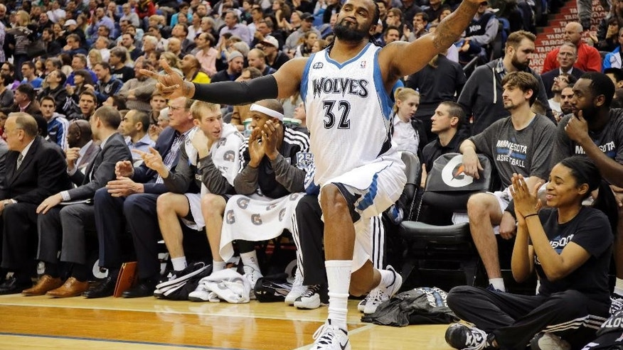 Minnesota Timberwolves center Ronny Turiaf (32), of France, reacts after teammate Ricky Rubio made a three-point basket during the second quarter of an NBA basketball game against the Utah Jazz in Minneapolis, Wednesday, April 16, 2014. (AP Photo/Ann Heisenfelt)