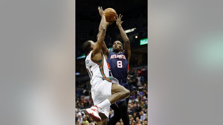 Atlanta Hawks' Shelvin Mack (8) shoots past Milwaukee Bucks' Chris Wright (15) during the first half of an NBA basketball game on Wednesday, April 16, 2014, in Milwaukee. (AP Photo/Morry Gash)
