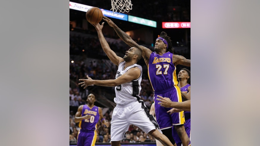 San Antonio Spurs' Tony Parker (9), of France, is pressured by Los Angeles' Jordan Hill (27) as he drives to the basket during the first half of an NBA basketball game, Wednesday, April 16, 2014, in San Antonio. (AP Photo/Eric Gay)