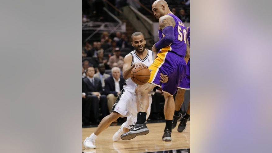 San Antonio Spurs' Tony Parker, left, of France, tries to drive around Los Angeles' Robert Sacre (50) during the first half of an NBA basketball game, Wednesday, April 16, 2014, in San Antonio. (AP Photo/Eric Gay)