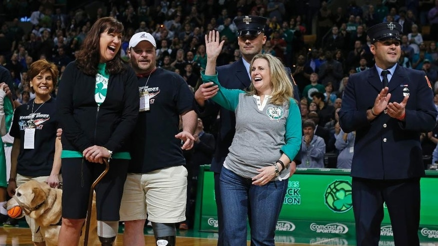 2013 Boston Marathon bombing survivor Roseann Sdoia waves to a cheering crowd as Karen Rand, front left, laughs as they and others are honored during a break in an NBA basketball game between the Boston Celtics and the Washington Wizards in Boston, Wednesday, April 16, 2014. (AP Photo/Elise Amendola)