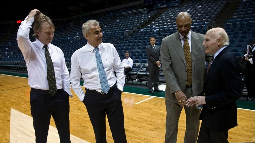 CORRECTS IDS ON BUYERS, WHICH WERE SWITCHED - LASRY IS AT CENTER LEFT - New York investment firm executives Marc Lasry, center left, and Wesley Edens, left, talk to Milwaukee Bucks assistant coach Jim Cleamons. second from right, and owner Herb Kohl, right, Wednesday, April 16, 2014, in Milwaukee. The Bucks announced that Kohl has reached a deal to sell the franchise to Edens and Lasry. (AP Photo/Morry Gash)