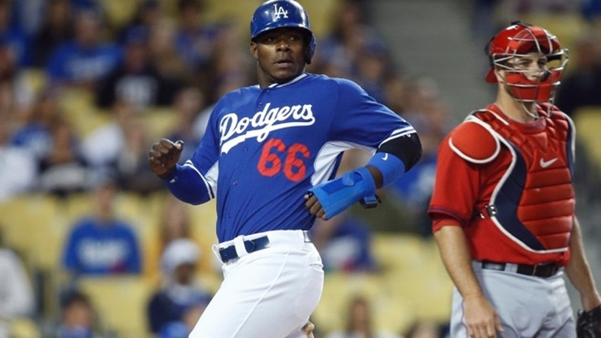 March 27, 2014: Los Angeles Dodgers' Yasiel Puig, left, scores past Los Angeles Angels catcher Chris Iannetta on a ball hit by Adrian Gonzalez during the second inning of an exhibition baseball game in Los Angeles.