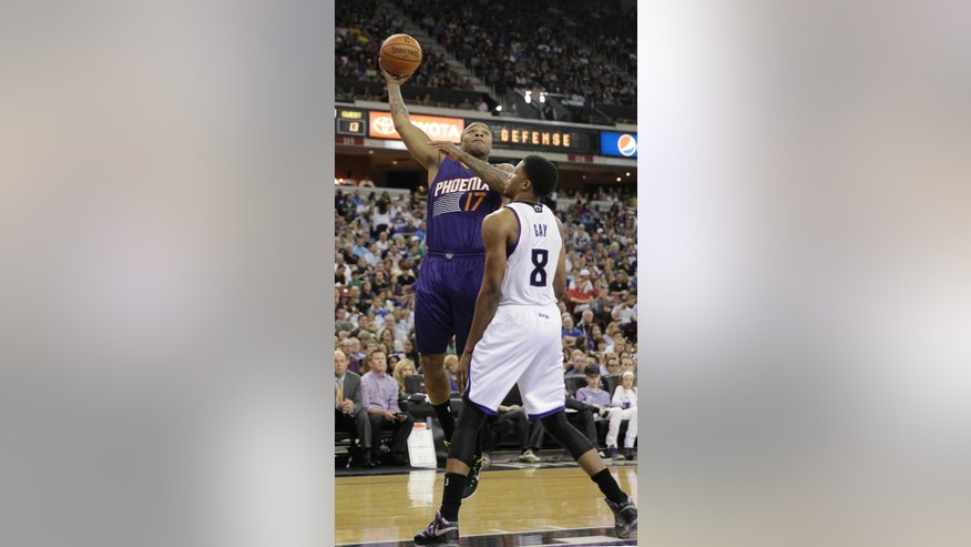 Phoenix Suns guard P.J. Tucker, left, shoots over Sacramento Kings forward Rudy Gay during the first quarter of an NBA basketball game in Sacramento, Calif., Wednesday, April 16, 2014. (AP Photo/Rich Pedroncelli)