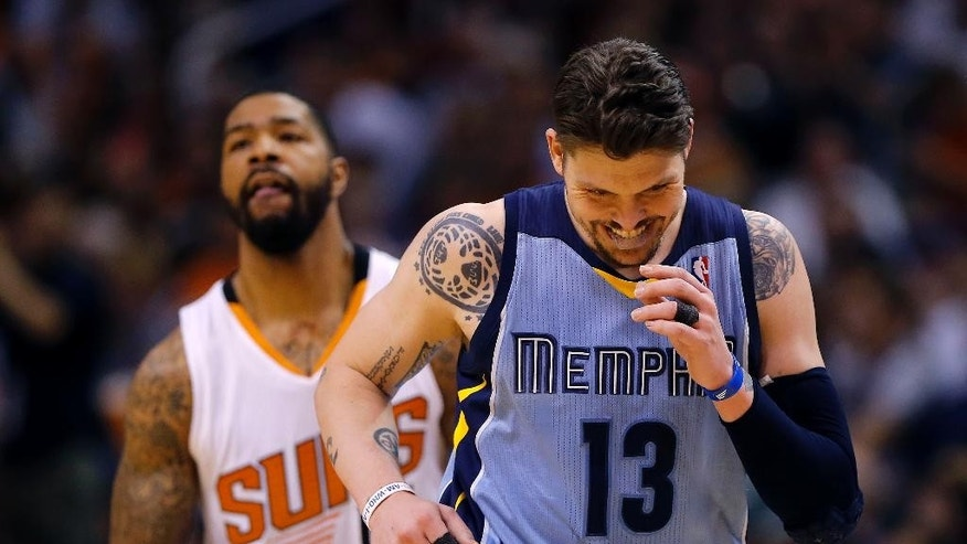 Memphis Grizzlies' Mike Miller (13) smiles after hitting a three-pointer as Phoenix Suns' Markeiff Morris looks away during the second half of an NBA basketball game, Monday, April 14, 2014, in Phoenix. The Grizzlies won 97-91. (AP Photo/Matt York)