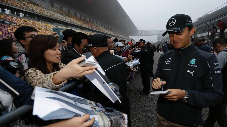 Mercedes driver Nico Rosberg of Germany, right, signs autographs for fans during an autograph session ahead of Sunday's Chinese Formula One Grand Prix at Shanghai International Circuit in Shanghai, China, Thursday, April 17, 2014. (AP Photo/Alexander F. Yuan)