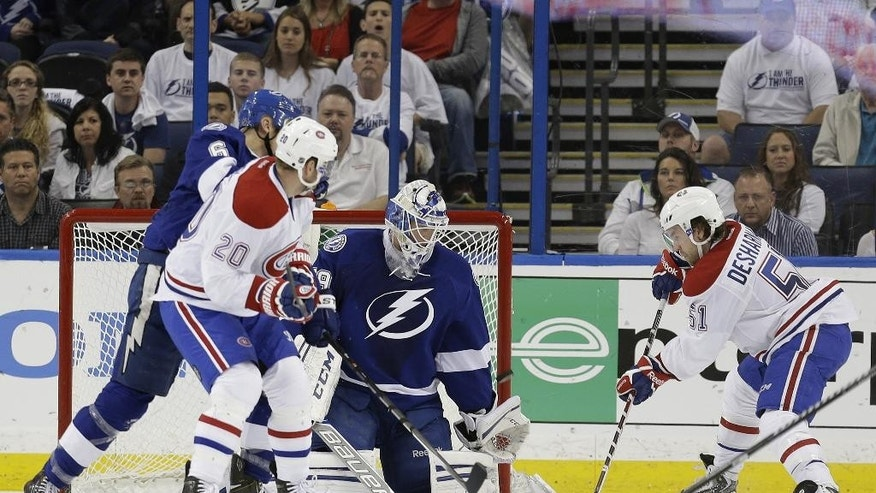CORRECTS TO SECOND PERIOD NOT FIRST PERIOD - Montreal Canadiens center David Desharnais (51) fires the puck past Tampa Bay Lightning goalie Anders Lindback (39), of Sweden, for a goal during the second period of Game 2 of a first-round NHL hockey playoff series on Friday, April 18, 2014, in Tampa, Fla. Canadiens' Thomas Vanek (20) and Lightning's Sami Salo (6), of Finland, look on. (AP Photo/Chris O'Meara)