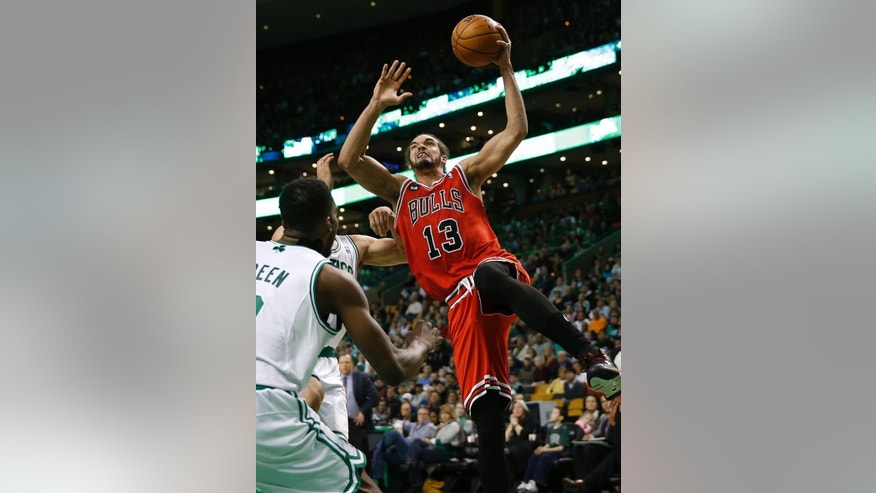 FILE - In this March 30, 2014 file photo, Chicago Bulls' Joakim Noah (13) goes to the basket as Boston Celtics' Jeff Green, left, defends in the first quarter of an NBA basketball game in Boston. Chicago wound up with 48 wins in a season that could have gone all wrong.  (AP Photo/Michael Dwyer, File)