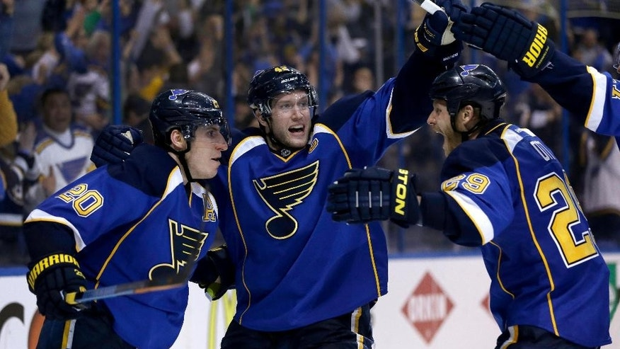 St. Louis Blues' Alexander Steen, left, is congratulated by teammates David Backes, center, and Steve Ott, right, after scoring the game-winning goal during the third overtime in Game 1 of a first-round NHL hockey Stanley Cup playoff series against the Chicago Blackhawks Thursday, April 17, 2014, in St. Louis. The Blues won 4-3 in triple overtime. (AP Photo/Jeff Roberson)
