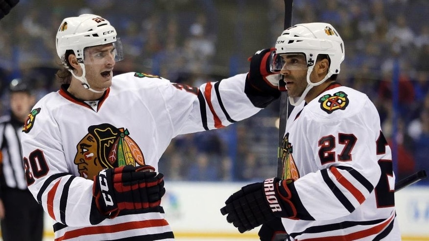 Chicago Blackhawks' Johnny Oduya, of Sweden, is congratulated by Brandon Saad, left, after scoring during the first period in Game 1 of a first-round NHL hockey Stanley Cup playoff series against the St. Louis Blues Thursday, April 17, 2014, in St. Louis. (AP Photo/Jeff Roberson)