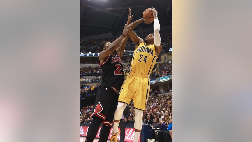 ADVANCE FOR WEEKEND EDITIONS, APRIL 19-20 - FILE - In this March 21, 2014 file photo, Indiana Pacers forward Paul George (24) shoots over Chicago Bulls guard Jimmy Butler in the second half of an NBA basketball game in Indianapolis. George has the pedigree to make it big in the NBA. But the question remains: Can one of the league's brightest young stars in one of the league's smallest cities still make it big in the marketing business.  (AP Photo/R Brent Smith, File)