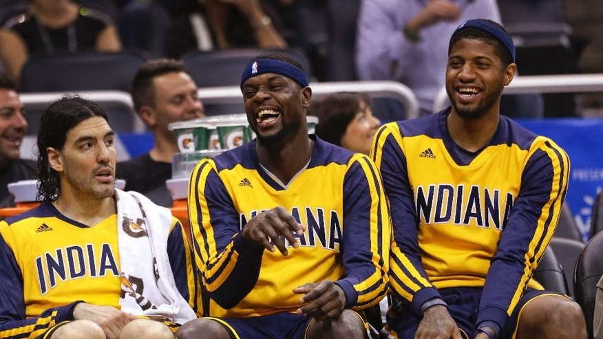 Indiana Pacers players, from left, Luis Scola, Lance Stephenson and Paul George share a laugh on the bench during the fourth quarter of an NBA basketball game in Orlando, Fla., Wednesday, April 16, 2014. Indiana won 101-86. (AP Photo/John Raoux)