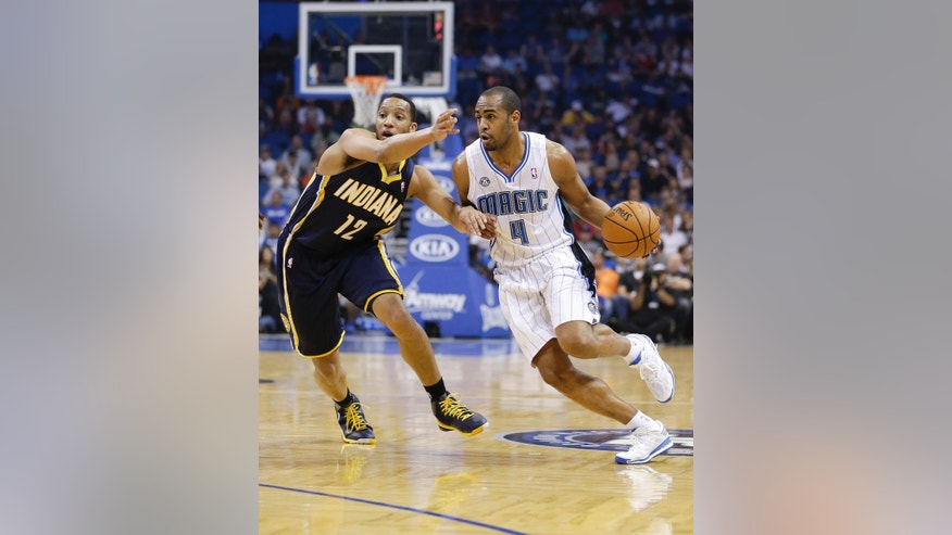 Orlando Magic's Arron Afflalo (4) drives around Indiana Pacers' Evan Turner (12) during the first half of an NBA basketball game in Orlando, Fla., Wednesday, April 16, 2014. (AP Photo/John Raoux)