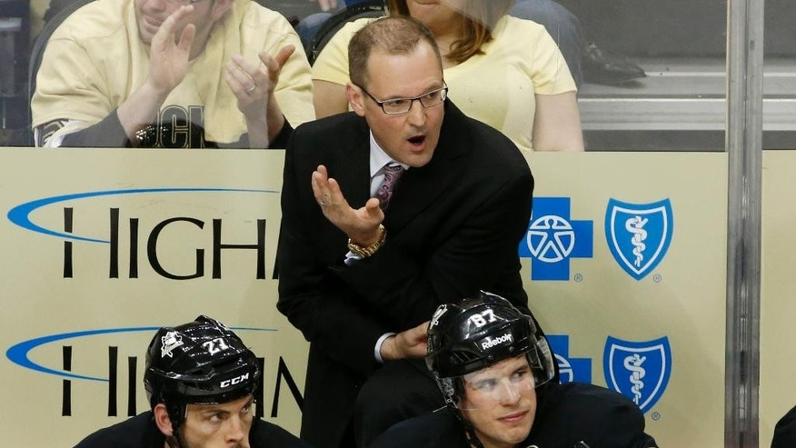 Pittsburgh Penguins coach Dan Bylsma talks with an official while standing behind Craig Adams (27) and Sidney Crosby (87) the third period of a first-round NHL playoff hockey game in Pittsburgh Wednesday, April 16, 2014. The Penguins defeated the Columbus Blue Jackets 4-3. (AP Photo/Gene J. Puskar)