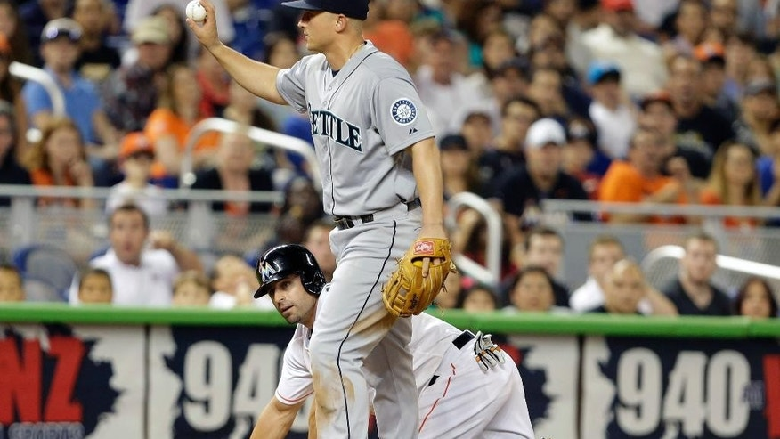 Seattle Mariners third baseman Kyle Seager holds up the ball after Miami Marlins' Reed Johnson was initially ruled out at third during the ninth inning of an interleague baseball game on2 Friday, April 18, 2014, in Miami. Seager was ruled safe after a replay review overturned the call. The Marlins defeated the Mariners 8-4.(AP Photo/Lynne Sladky)