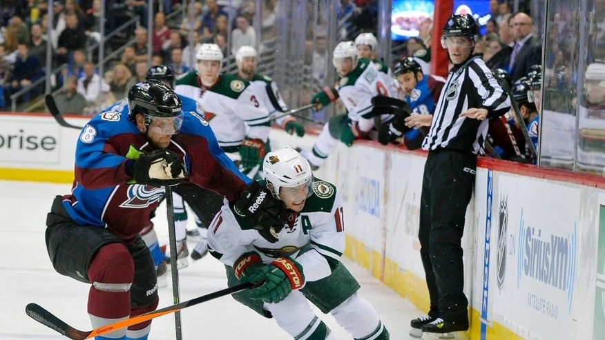 Colorado Avalanche defenseman Jan Hejda (8), from the Czech Republic, hits Minnesota Wild left wing Zach Parise (11) in the chin during the first period in Game 1 of an NHL hockey first-round playoff series on Thursday, April 17, 2014, in Denver. (AP Photo/Jack Dempsey)