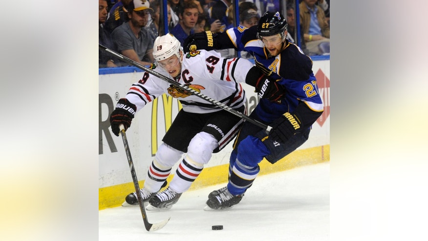 St. Louis Blues' Alex Pietrangelo (27) and Chicago Blackhawks' Jonathan Toews (19) battle for the puck during the first period in Game 2 of a first-round NHL hockey playoff series, Saturday, April 19, 2014, in St. Louis. (AP Photo/Bill Boyce)