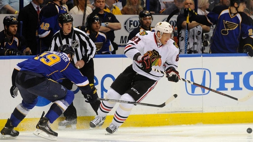 Chicago Blackhawks' Marian Hossa (81), of Sweden, and St. Louis Blues' Jay Bouwmeester (19) reach for a loose puck during the first period in Game 2 of a first-round NHL hockey playoff series on Saturday, April 19, 2014, in St. Louis. (AP Photo/Bill Boyce)