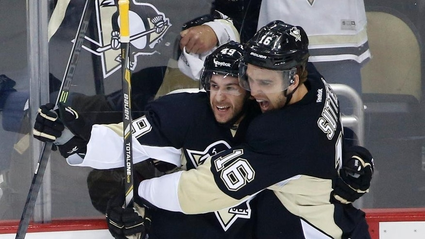 Pittsburgh Penguins' Brian Gibbons (49) celebrates his second goal of the first period with teammate Brandon Sutter (16) during a first-round NHL playoff hockey game against the Columbus Blue Jackets in Pittsburgh on Saturday, April 19, 2014. (AP Photo/Gene J. Puskar)