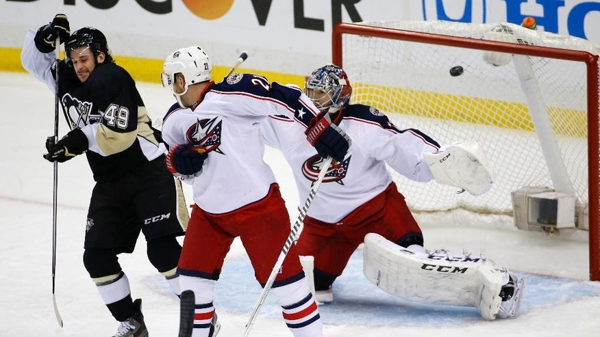 Pittsburgh Penguins' Brian Gibbons (49) deflects a shot over Columbus Blue Jackets goalie Sergei Bobrovsky (72) for a goal in the first period of a first-round NHL playoff hockey game in Pittsburgh on Saturday, April 19, 2014. (AP Photo/Gene J. Puskar)