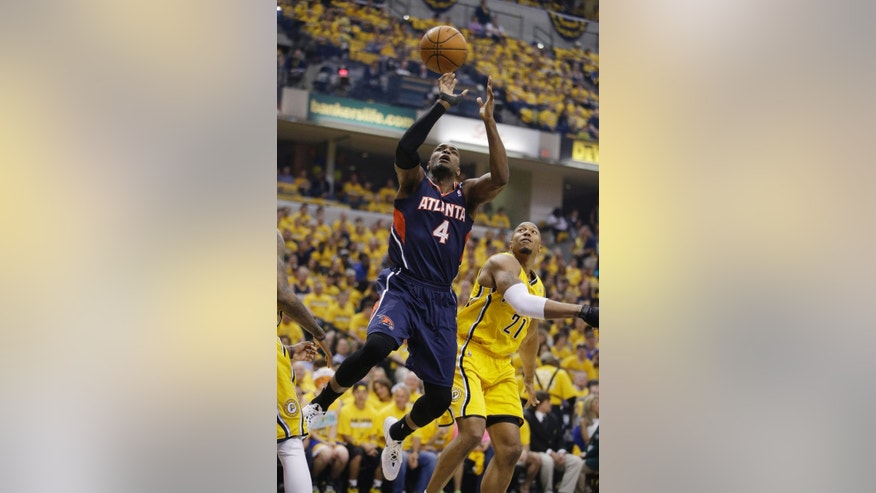 Atlanta Hawks' Paul Millsap (4) shoots against Indiana Pacers' David West during the first half in Game 1 of an opening-round NBA basketball playoff series on Saturday, April 19, 2014, in Indianapolis. (AP Photo/Darron Cummings)