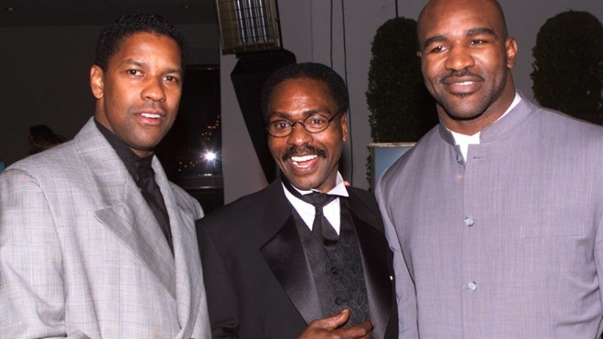"Dec. 14, 1999: Actor Denzel Wahington (L), star of the film ""The Hurricane,"" based on the true story of Rubin ""Hurricane"" Carter (C), an innocent man who fought for 20 years for justice, poses at the film's premiere party  in Los Angeles with boxing champion Evander Holyfield."
