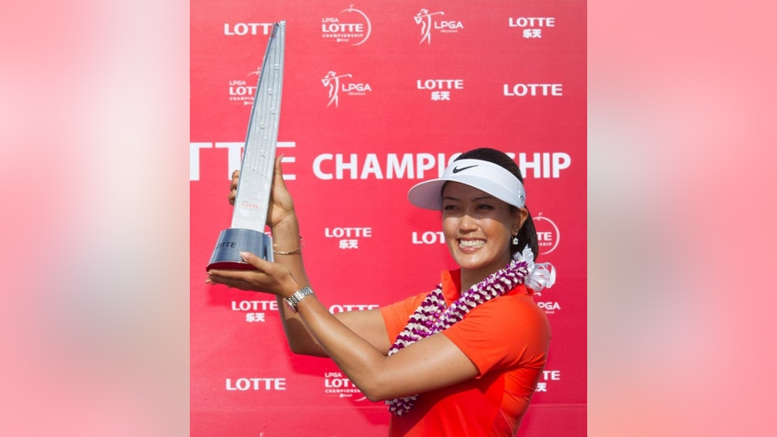 Michelle Wie holds up the 2014 LPGA LOTTE Championship trophy at Ko Olina Golf Club, Saturday, April 19, 2014, in Kapolei, Hawaii. (AP Photo/Eugene Tanner)