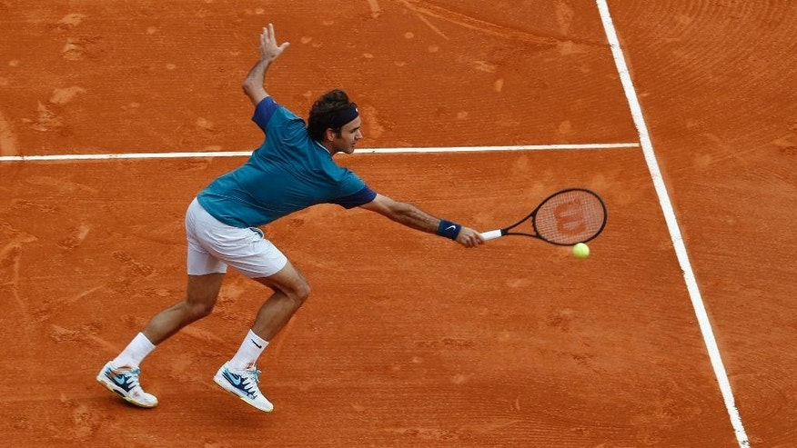 Roger Federer of Switzerland, returns the ball to Stanislas Wawrinka of Switzerland during the final match of the Monte Carlo Tennis Masters tournament in Monaco, Sunday, April 20, 2014. (AP Photo/Michel Euler)