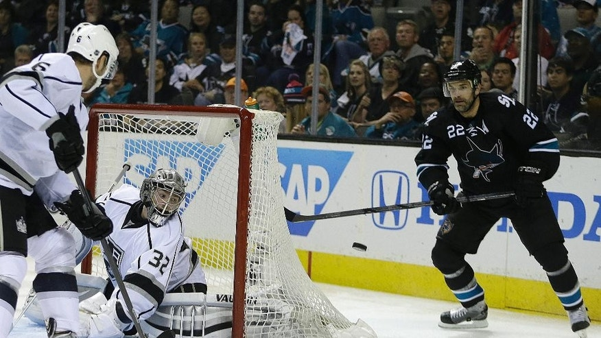 San Jose Sharks' Dan Boyle, right, moves the puck behind the net as Los Angeles Kings goalie Jonathan Quick defends during the second period of Game 2 of an NHL hockey first-round playoff series Sunday, April 20, 2014, in San Jose, Calif. (AP Photo/Ben Margot)