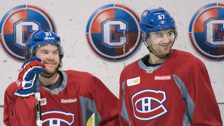 Montreal Canadiens' David Desharnais, left, and Max Pacioretty chat during a practice session in Brossard, Quebec,  Monday, April 21, 2014. The Canadiens lead Tampa Bay 3-0 in their best-of-seven series in the first round of the playoffs. (AP Photo/The Canadian Press, Graham Hughes)