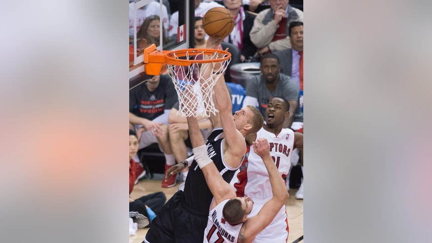 Brooklyn Nets' Mason Plumlee, left, puts back a rebound between Toronto Raptors' Jonas Valanciunas, front, and Terrence Ross during the second half of Game 1 of an opening-round NBA basketball playoff series, in Toronto on Saturday, April 19, 2014. The Nets won 94-87. (AP Photo/The Canadian Press, Darren Calabrese)