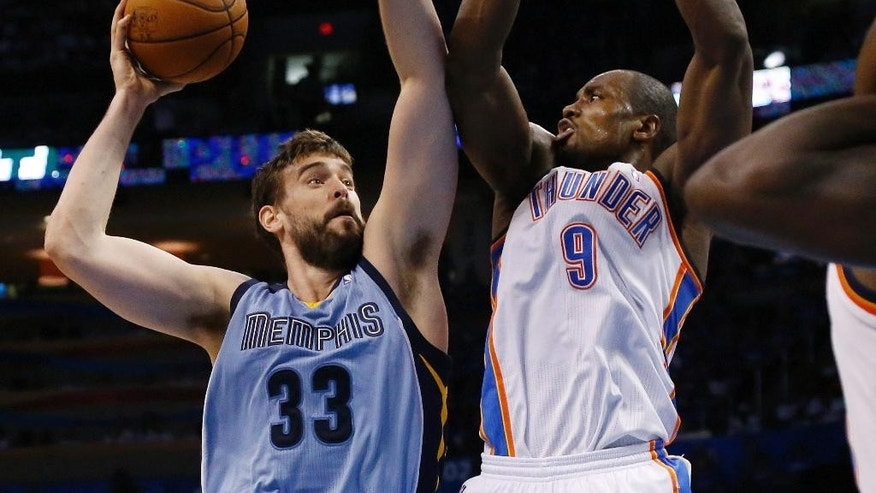 Memphis Grizzlies center Marc Gasol (33) shoots as Oklahoma City Thunder forward Serge Ibaka (9) defends in the second quarter of Game 2 of an opening-round NBA basketball playoff series in Oklahoma City, Monday, April 21, 2014. (AP Photo/Sue Ogrocki)