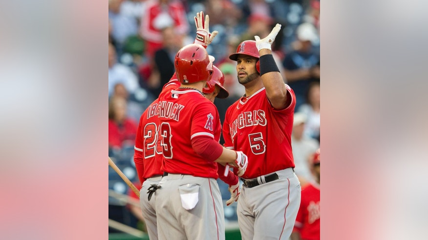 Los Angeles Angels Albert Pujols (5) is greeted at home by teammates J.B. Shuck (3) and Raul Ibanez (28) after hitting a three-run homer off Washington Nationals starting pitcher Taylor Jordan during the first inning of a baseball game in Washington, Tuesday, April 22, 2014. This was Pujos 499th home run of his career. (AP Photo/Pablo Martinez Monsivais)