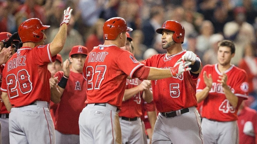 Los Angeles Angels Albert Pujols (5) is greeted by Mike Trout (27) and other teammates at home plate after hitting a two-run homer against Washington Nationals Taylor Jordan in the fifth inning of a baseball game in Washington, Tuesday, April 22, 2014. This was Pujols 500th career home run. (AP Photo/Pablo Martinez Monsivais)