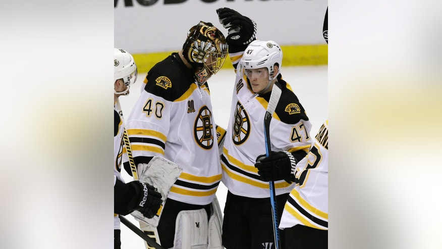 Boston Bruins defenseman Torey Krug (47) pats the head of goalie Tuukka Rask (40) of Finland after the third period of Game 3 of a first-round NHL hockey playoff series against the Detroit Red Wings in Detroit, Tuesday, April 22, 2014. The Bruins defeated the Red Wings, 3-0. (AP Photo/Carlos Osorio)