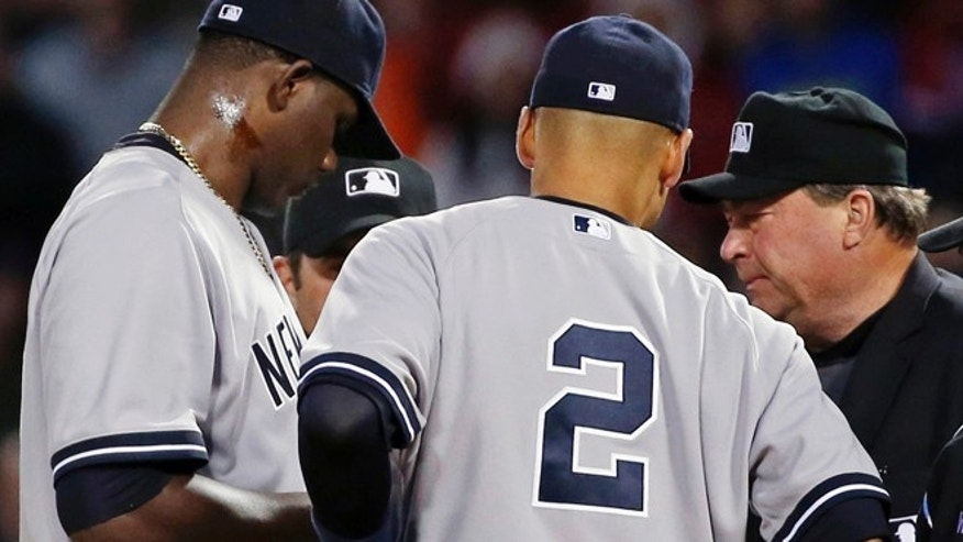 April 23, 2014: Home plate umpire Gerry Davis, right, confers on the mound with New York Yankees starting pitcher Michael Pineda, left, and shortstop Derek Jeter, center, and others in the second inning of a baseball game against the Boston Red Sox at Fenway Park in Boston.