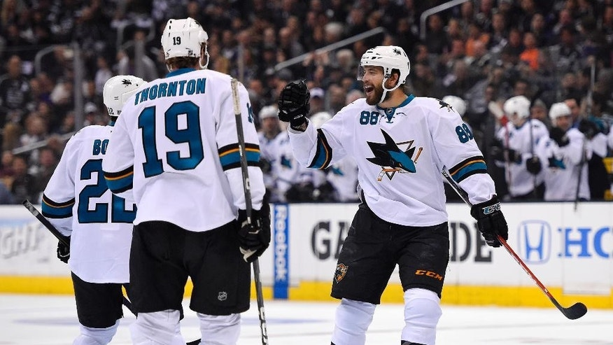 San Jose Sharks right wing Brent Burns, right, celebrates his goal with teammates defenseman Dan Boyle, left, and center Joe Thornton during the first period in Game 3 of an NHL hockey first-round playoff series , Tuesday, April 22, 2014, in Los Angeles. (AP Photo/Mark J. Terrill)