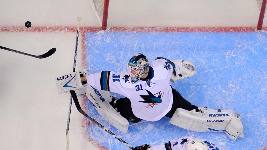 San Jose Sharks goalie Antti Niemi, top, of Finland, deflects a shot as defenseman Justin Braun reaches in during the first period in Game 3 of an NHL hockey first-round playoff series  against the Los Angeles Kings, Tuesday, April 22, 2014, in Los Angeles. (AP Photo/Mark J. Terrill)
