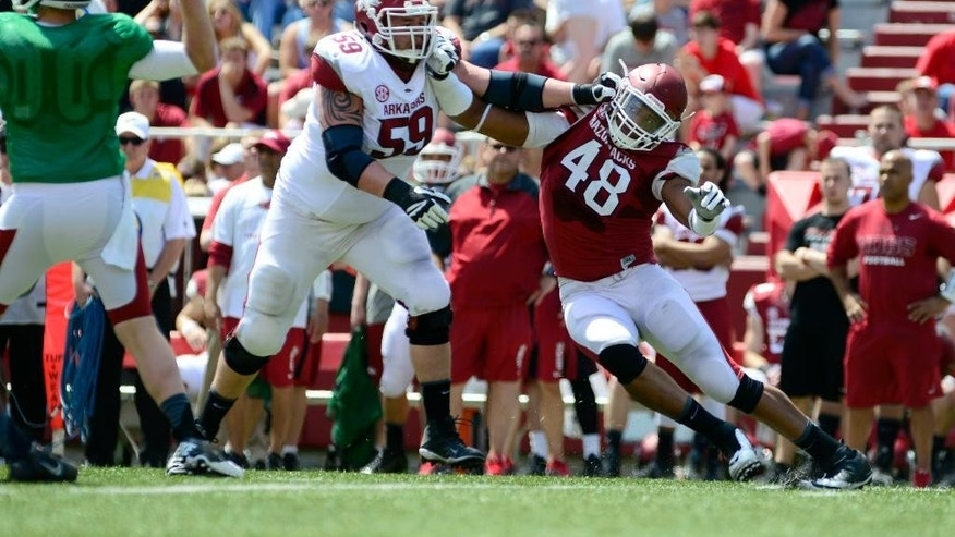 Arkansas defensive end Deatrich Wise Jr. (48) moves around offensive guard Marcus Danenhauer (59) in the first half of  their spring NCAA college football game in Fayetteville, Ark., Saturday, April 26, 2014. (AP Photo/Sarah Bentham)