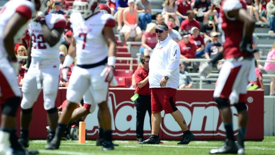 Arkansas head coach Bret Bielema, back center, observes his players on the field during their spring NCAA college football game, Saturday, April 26, 2014, in Fayetteville, Ark. (AP Photo/Sarah Bentham)