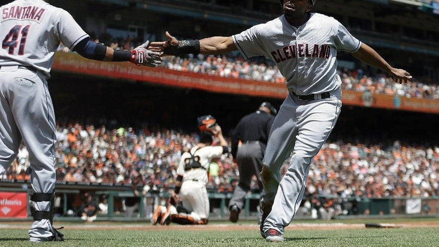 Cleveland Indians' Michael Bourn, right, is congratulated by teammate Carlos Santana (41) after scoring against the San Francisco Giants in the first inning of a baseball game on Saturday, April 26, 2014, in San Francisco. Bourn scored on a single by Jason Kipnis. (AP Photo/Ben Margot)