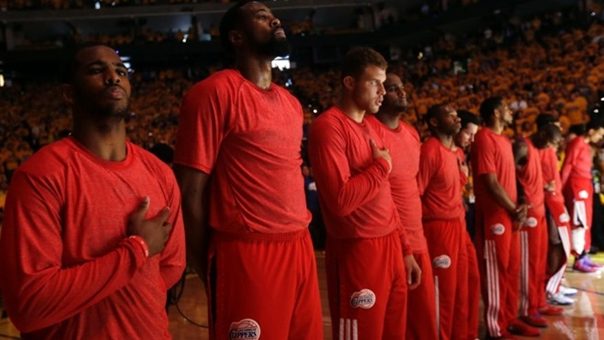 April 27, 2014: Members of the Los Angeles Clippers listen to the national anthem before Game 4 of an opening-round NBA basketball playoff series against the Golden State Warriors in Oakland, Calif.