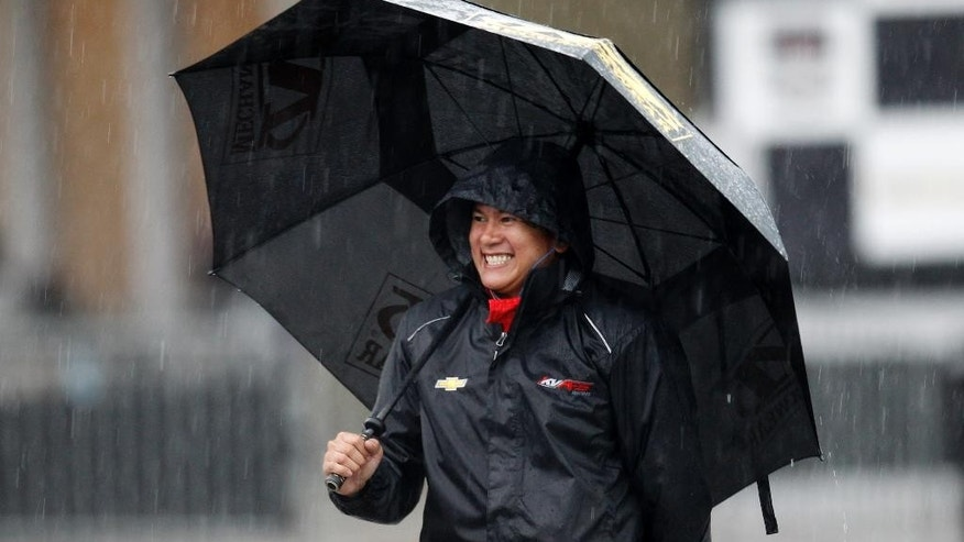 Sebastian Saavedra, of Colombia, walks through the garage area as a severe storm delays the Indy Grand Prix of Alabama auto race on Sunday, April 27, 2014, in Birmingham, Ala. (AP Photo/Butch Dill)