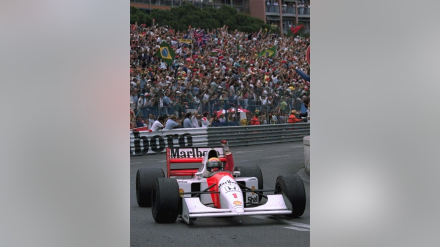 FILE - In this May 31, 1992 file photo, Brazilian driver Ayrton Senna raises his fist to salute the crowd after he won the Monaco Formula One Grand Prix on his McLaren-Honda. Brazil's adoration of Ayrton Senna transcends sports. Senna won three Formula One titles — in 1988, 1990 and '91 — all with McLaren. He moved to the Williams team for his tragic 1994 season. Despite his career being cut short when he was 34, his 41 wins stand third all-time behind Michael Schumacher's 91 and rival Alain Prost's 51. He died at the 1994 San Marino Grand Prix. (AP Photo/JEAN-MARC FOLLETE, File)