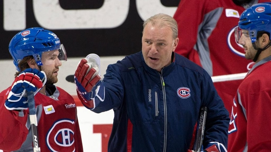 Montreal Canadiens head coach Michel Therrien goes over a play with Montreal Canadiens center David Desharnais, left, and left wing Max Pacioretty, right, during the team's NHL hockey practice Monday, April 28, 2014, in Brossard, Quebec. (AP Photo/The Canadian Press, Ryan Remiorz)