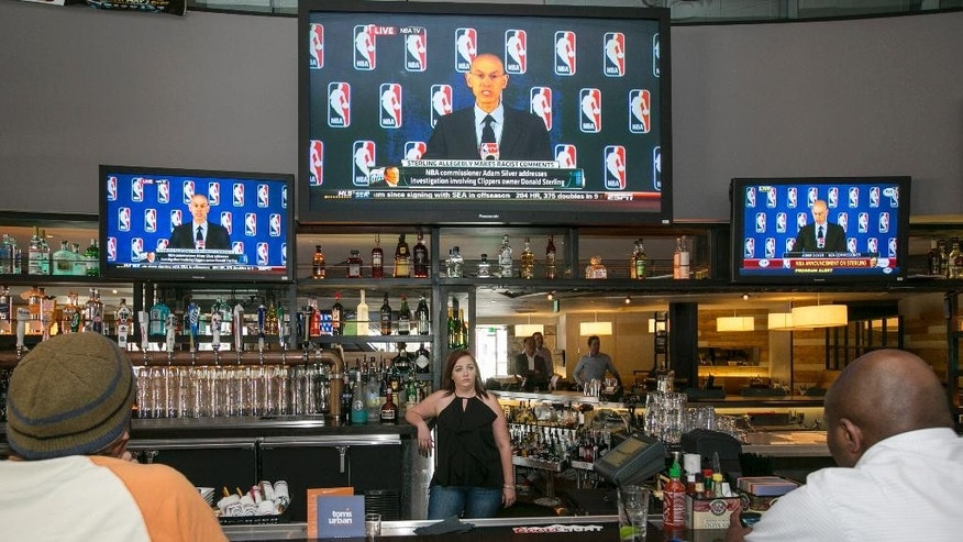 Sport fans watch television monitors at a restaurant in Los Angeles Tuesday, April 26, 2014, showing a live broadcast of NBA Commissioner Adam Silver's news conference in New York. Silver announced that Los Angeles Clippers owner Donald Sterling has been banned for life by the league in response to racist comments the league says he made in a recorded conversation. (AP Photo)