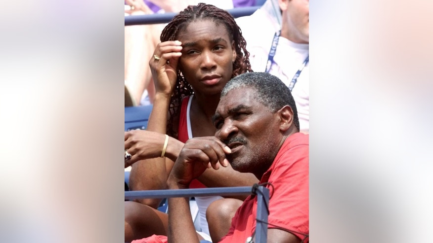 "FILE - In this Sept. 4, 2000, file photo, Venus Williams watches her sister Serena play Australia's Jelena Dokic alongside her father and coach Richard Williams at the U.S. Open tennis tournament in New York. His new book, ""Black and White: The Way I See It,"" comes out May 6. It goes into detail about how Indian Wells, as he writes, ""disgraced America."" (AP Photo/Suzanne Plunkett, File)"