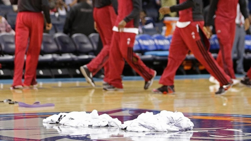 Warm-up shirts are piled at center court as Miami Heat players prepare for Game 4 of an opening-round NBA basketball playoff series against the Charlotte Bobcats in Charlotte, N.C., Monday, April 28, 2014. (AP Photo/Chuck Burton)