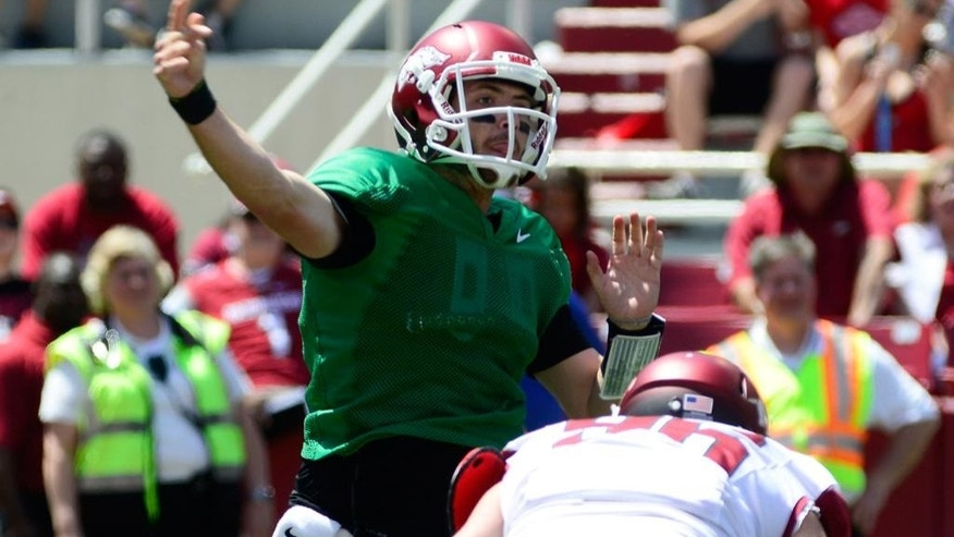 Arkansas quarterback Brandon Allen, left, delivers a pass during their spring NCAA football game, Saturday, April 26, 2014, in Fayetteville, Ark. (AP Photo/Sarah Bentham)